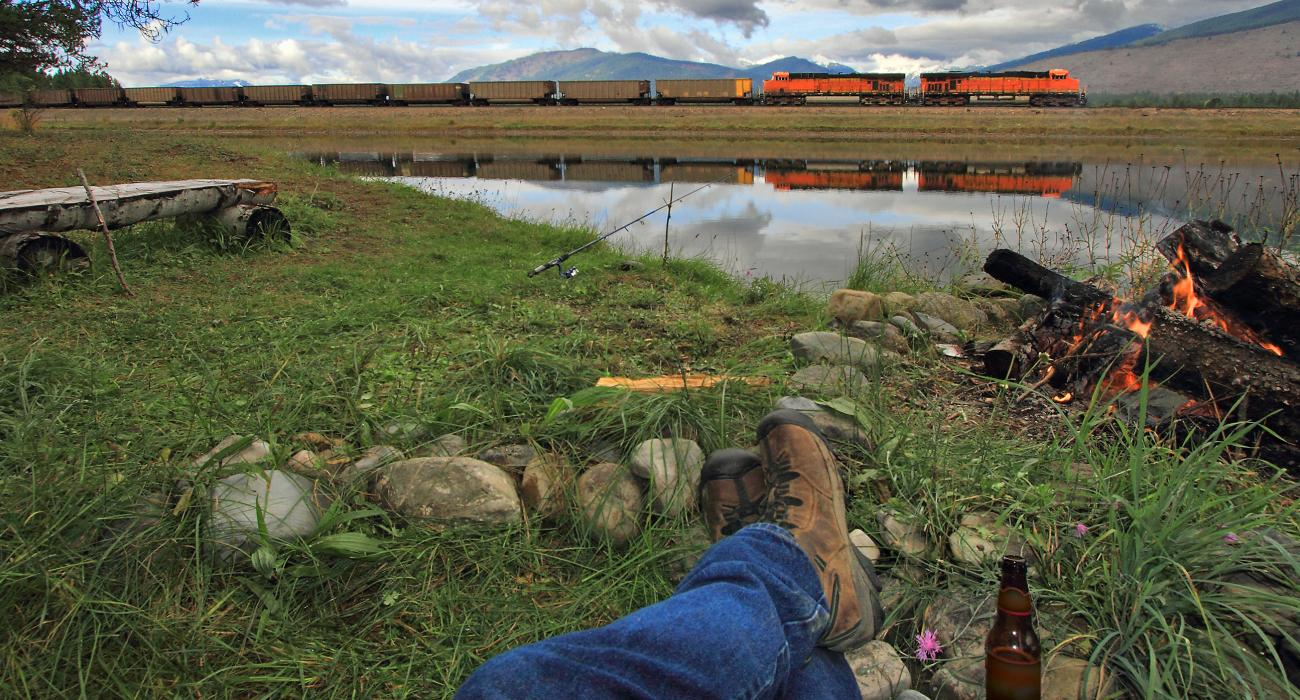 Relaxing In Front Of Campfire As Train Passes By Frog Pond In Montana