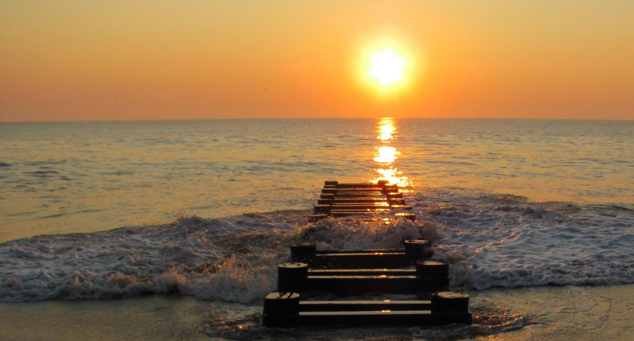 Setting Sun As The Surf Rolls In On An Abandoned Pier