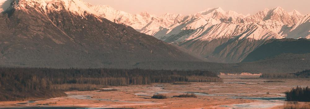 Sunlit, snow-capped mountains in Alaska